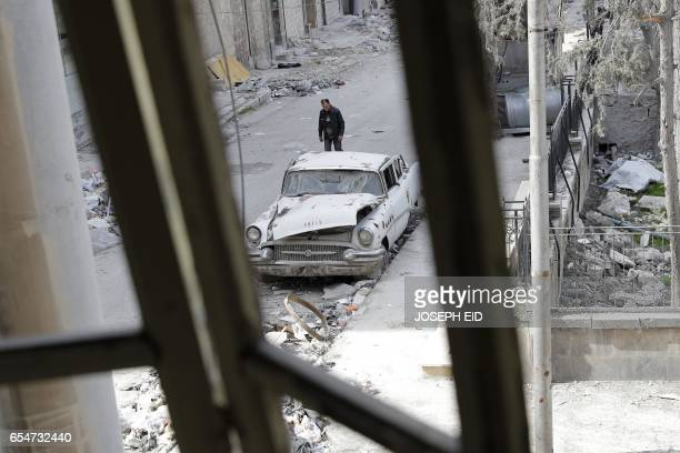 TOPSHOT A picture taken on March 9 shows a Syrian man walking past a 1955 Buick Super parked outside the home of Mohammed Mohiedin Anis or Abu Omar...