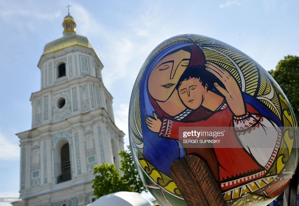 A picture taken on May 1, 2016 in front of Saint Sophiya cathedral in Kiev shows a Pysanka, a traditional Easter egg, decorated by Ukrainian artists to celebrate Orthodox Easter and spring time. 374 big eggs and 40,000 smaller one are presented at St. Sophiya Square in Kiev for the occasion. / AFP / Sergei SUPINSKY