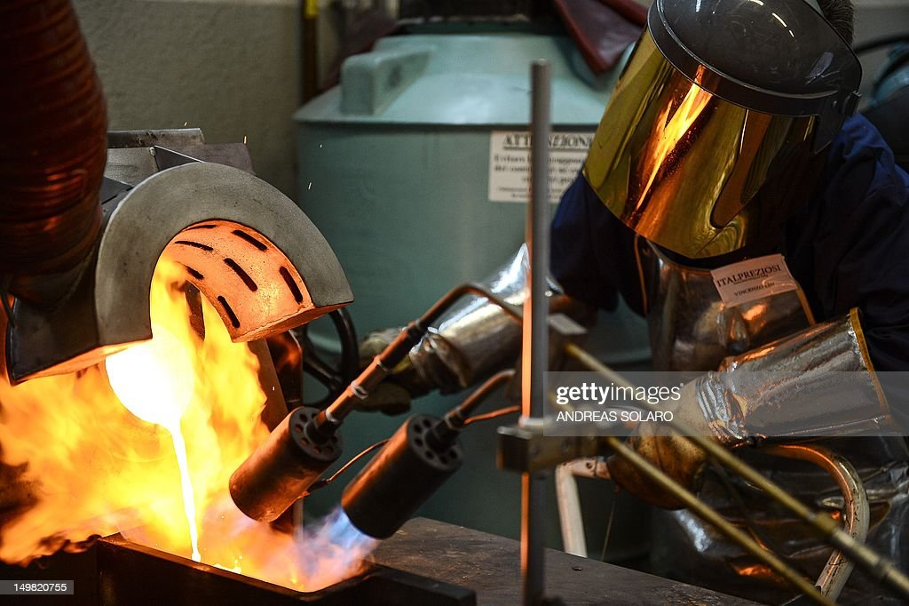 A picture taken on May 11, 2012 shows a goldsmih controlling the fire during the melting of gold to produce a gold ingot, at Italpreziosi gold refinery company, in Arezzo. Italy's traditional goldsmiths are up in arms over a boom in the poorly regulated cash-for-gold sector that is making billions for the mafia as hard-up Italians rush to sell off their bling. Cash-for-gold shops have filled Italy's streets in recent months and even popped up on the historic Ponte Vecchio in Florence, with blanket television adverts urging Italians to sell off their medallions and jewels for quick cash.