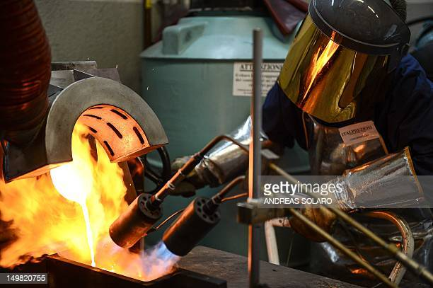 A picture taken on May 11 2012 shows a goldsmih controlling the fire during the melting of gold to produce a gold ingot at Italpreziosi gold refinery...