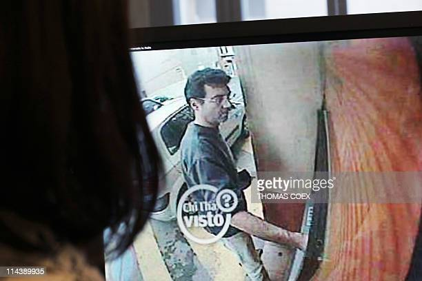 A picture taken on May 11 in Paris shows a woman looking at a still frame taken from a surveillance camera and released on the Italian RAI TV website...