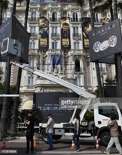 A picture taken on May 11 shows technicians displaying promotional billboards on the facade of the Carlton Hotel on the Croisette in Cannes...