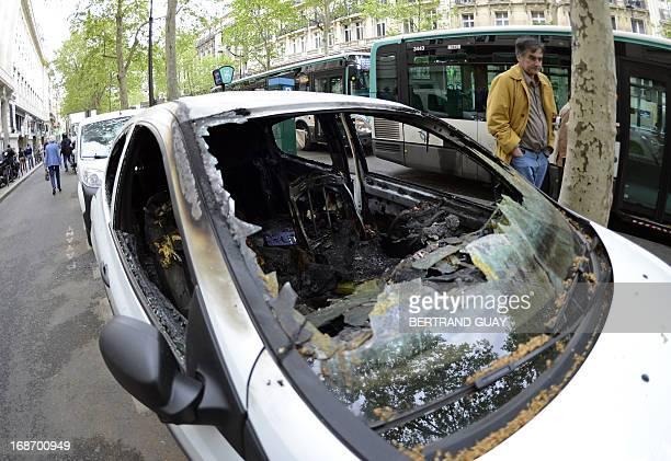 A picture taken on May 14 2013 in Paris shows broken windows of a car partially burnt following clashes the night before when up to 15000 Paris...