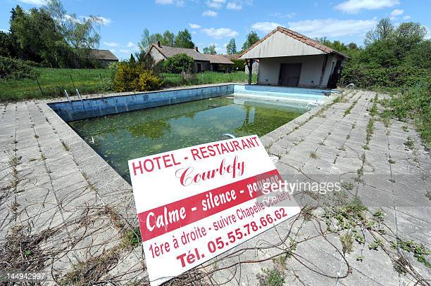 A picture taken on May 16 2012 shows the swimming pool of a hotel resort in SaintNicolasCourbefy village in central France which was abandoned by its...