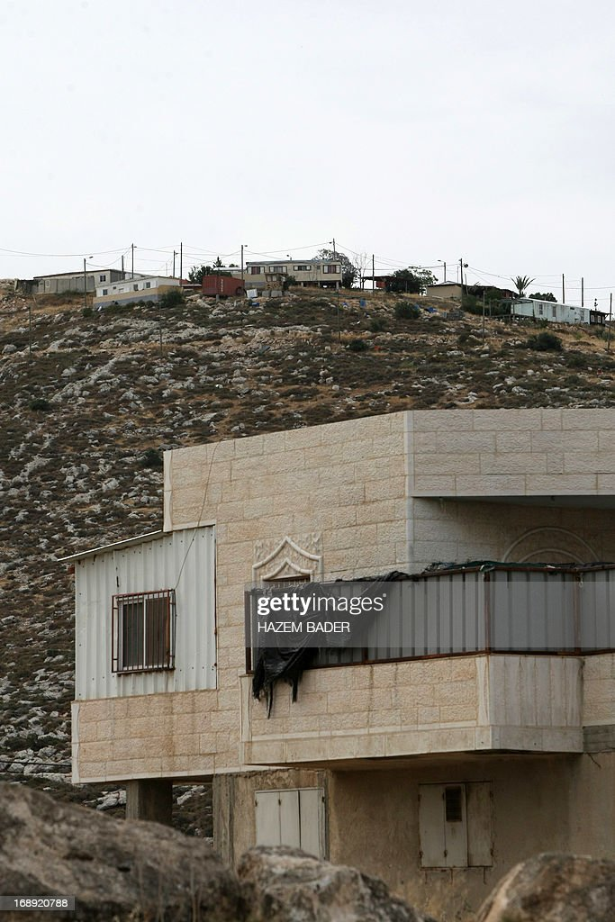 A picture taken on May 17, 2013 shows a house belonging to Palestinians in front of houses in the Mitzpe Lachish Israeli settlement outpost (background) in the West Bank village of Beit Awwa. Israeli settlement watchdog Peace Now said on May 16, 2013 that the government wants to give retroactive approval to four West Bank settlement outposts it had previously pledged to at least partially demolish. Givat Assaf, Givat HaRoeh, Maaleh Rehavam and Mitzpe Lachish outposts are among six listed in a 2005 government report as deserving immediate eviction and later ordered shut by a court order.