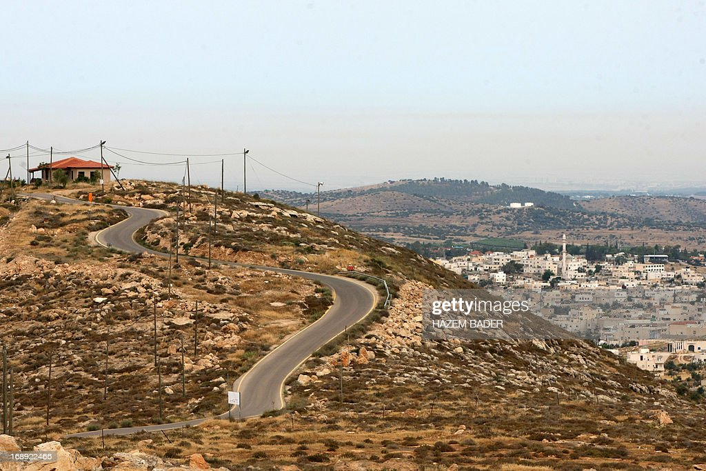 A picture taken on May 17, 2013 shows a house in the Mitzpe Lachish Israeli settlement outpost (L) in front of the West Bank village of Beit Awwa (R). Israeli settlement watchdog Peace Now said on May 16, 2013 that the government wants to give retroactive approval to four West Bank settlement outposts it had previously pledged to at least partially demolish. Givat Assaf, Givat HaRoeh, Maaleh Rehavam and Mitzpe Lachish outposts are among six listed in a 2005 government report as deserving immediate eviction and later ordered shut by a court order. AFP PHOTO / HAZEM BADER