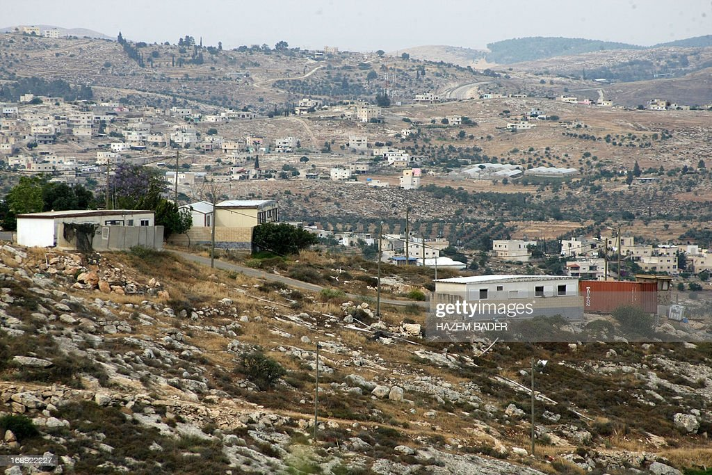 A picture taken on May 17, 2013 shows houses in the Mitzpe Lachish Israeli settlement outpost in front of house belonging to Palestinians (background) in the West Bank village of Beit Awwa. Israeli settlement watchdog Peace Now said on May 16, 2013 that the government wants to give retroactive approval to four West Bank settlement outposts it had previously pledged to at least partially demolish. Givat Assaf, Givat HaRoeh, Maaleh Rehavam and Mitzpe Lachish outposts are among six listed in a 2005 government report as deserving immediate eviction and later ordered shut by a court order.
