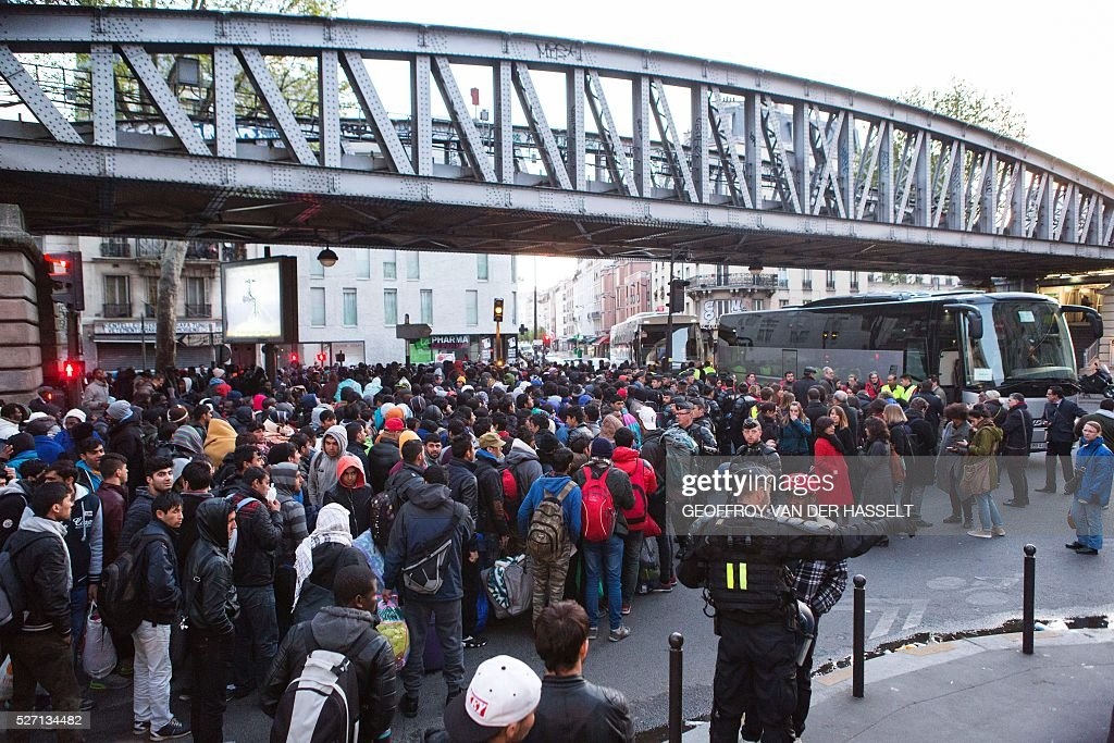 A picture taken on May 2, 2016 shows migrants being evacuated by French police officers and gendarmes from a makeshift camp under the Stalingrad metro station in Paris. / AFP / Geoffroy Van der Hasselt