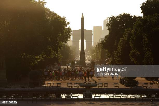 A picture taken on May 20 2015 shows people jogging after work in the Tuileries public park at sunset in Paris AFP PHOTO / LUDOVIC MARIN