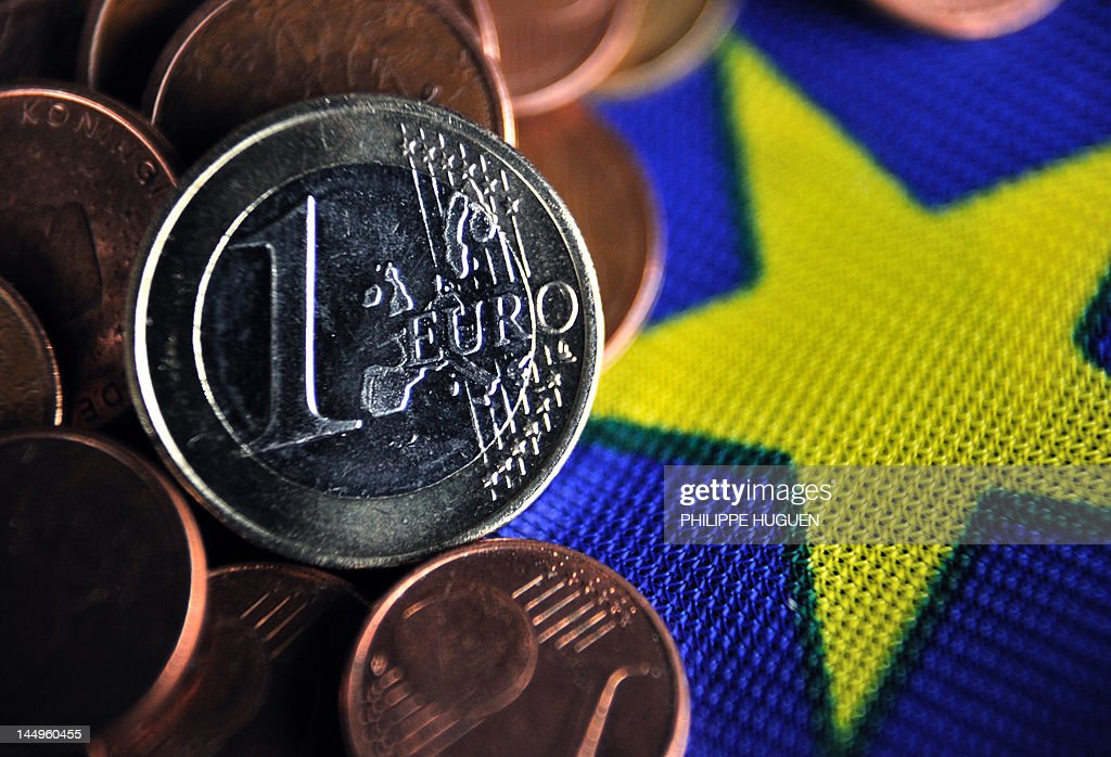 A picture taken on May 21, 2012 in the French northern city of Lille, shows a 1 euro coin and a pile of eurocents displayed on the European flag.