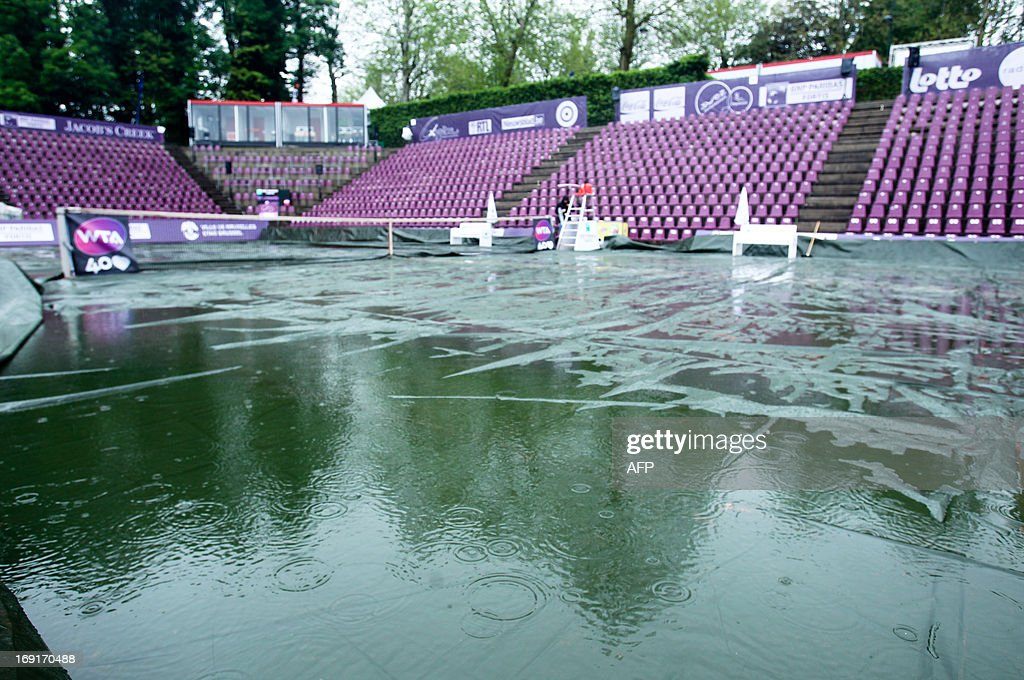 A picture taken on May 21, 2013 shows the court covered with a tarpaulin as rain falls delay the start of the Brussels WTA tennis Open.