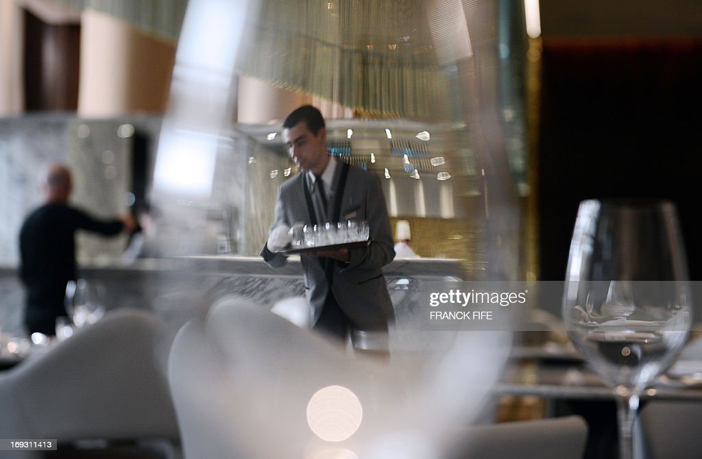 A picture taken on May 22, 2013, shows a server as seen through a wine glass at the restaurant 'La Scene' of the luxury hotel 'Prince de Galles' (Prince of Wales) in Paris. The Prince de Galles, on the Avenue George V in Paris reopened on May 16, 2013 under the 'Luxury Collection' brand after two years of renovation. The luxury hotel, with 159 rooms, a restaurant and bar, was built in 1928 and was closed since February 2011. The hotel received a fifth star on its reopening.