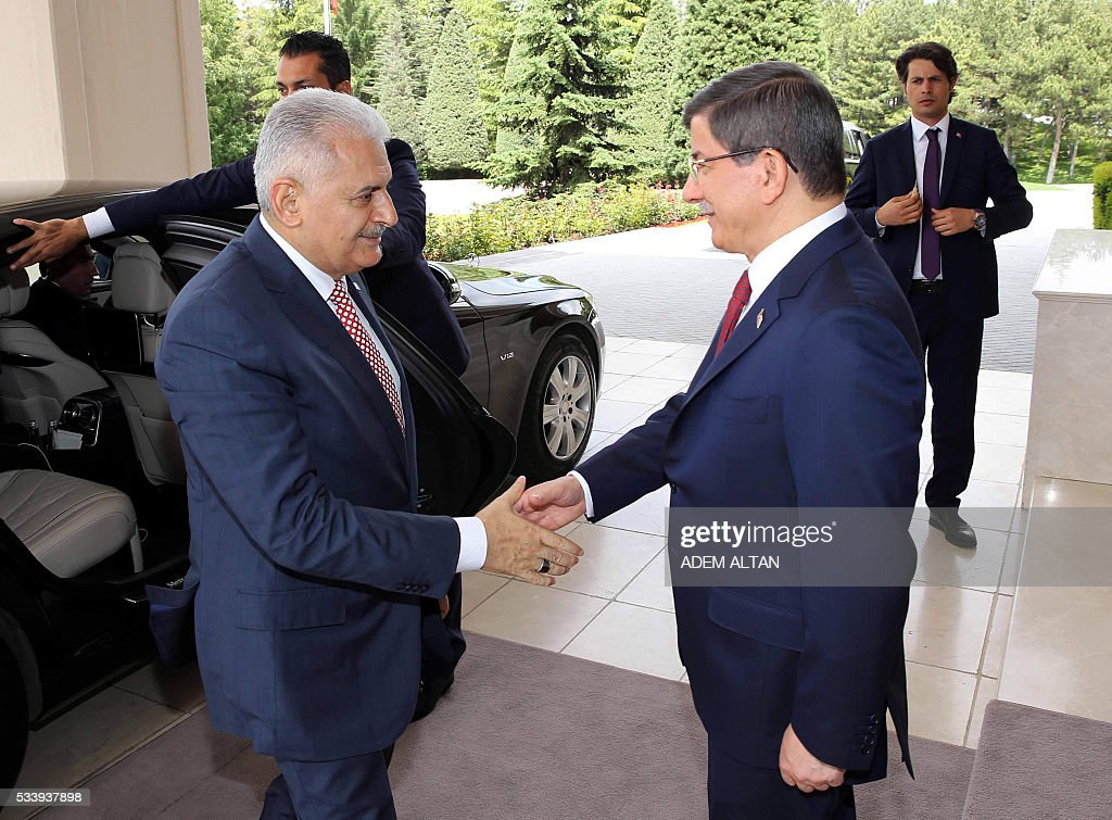 A picture taken on May 24, 2016 in Ankara shows Turkey's newly appointed Prime Minister and leader of AKP, Turkey's ruling party Binali Yildrim (L) speaking with outgoing Prime Minister Ahmet Davutoglu (R) during the handover ceremony at Cankaya Palace. / AFP / ADEM