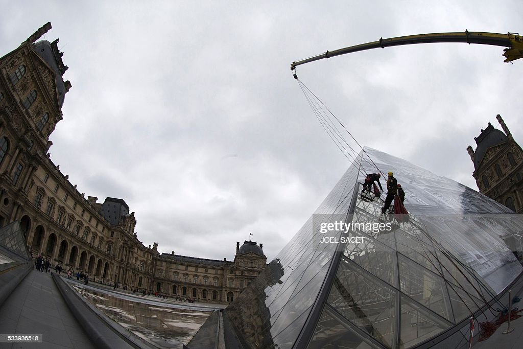 A picture taken on May 24, 2016 in Paris shows employees at work to cover the Louvre Pyramid with a giant photograph of the museum by French artist and photographer JR. Invited by the Louvre, the artist intends to tranform one of the Louvres symbols, the Pyramid, into a monumental optical illusion with 'a surprising anamorphic image', according to the museum. / AFP / JOEL