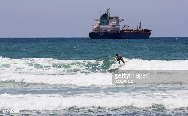 A picture taken on May 24 2017 shows 17yearold Syrian refugee Ali Kassem surfing off the shore of the town of Jiyeh south of the Lebanese capital...