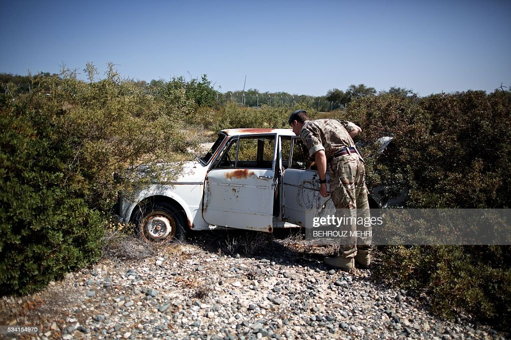A picture taken on May 25, 2016 shows a British soldier inspecting an abandoned vehicle parked at the Sovereign Base Area of Akrotiri, a British overseas territory located ten kilometres west of the Cypriot port city of Limassol. Abandoned in the streets of the base after the war, hundreds of vehicles that belonged to Turkish Cypriots, mostly dating from the 1960s, had been gathered in a vast wasteland in 1975 await their owners on the British base of Akrotiri, 42 years after being left behind in the divided island. The British authorities have recently undertaken an inventory of 400 vehicles in the hope of regaining their former owners, listing images and details of them on an internet site. / AFP / BEHROUZ