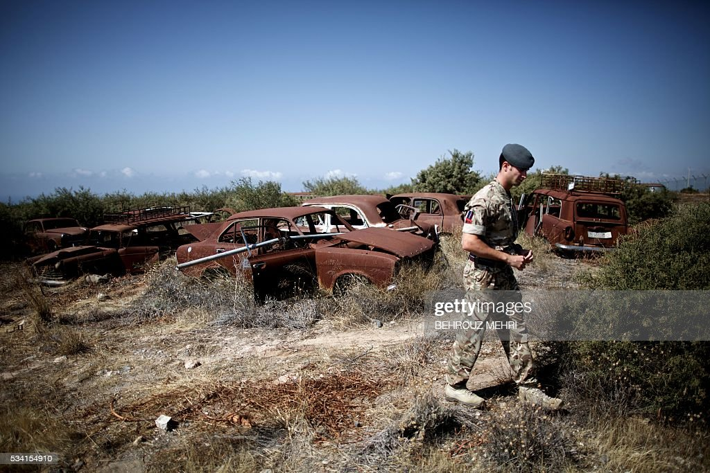 A picture taken on May 25, 2016 shows a British soldier walk past abandoned vehicles at the Sovereign Base Area of Akrotiri, a British overseas territory located ten kilometres west of the Cypriot port city of Limassol. Abandoned in the streets of the base after the war, hundreds of vehicles that belonged to Turkish Cypriots, mostly dating from the 1960s, had been gathered in a vast wasteland in 1975 await their owners on the British base of Akrotiri, 42 years after being left behind in the divided island. The British authorities have recently undertaken an inventory of 400 vehicles in the hope of regaining their former owners, listing images and details of them on an internet site. / AFP / BEHROUZ