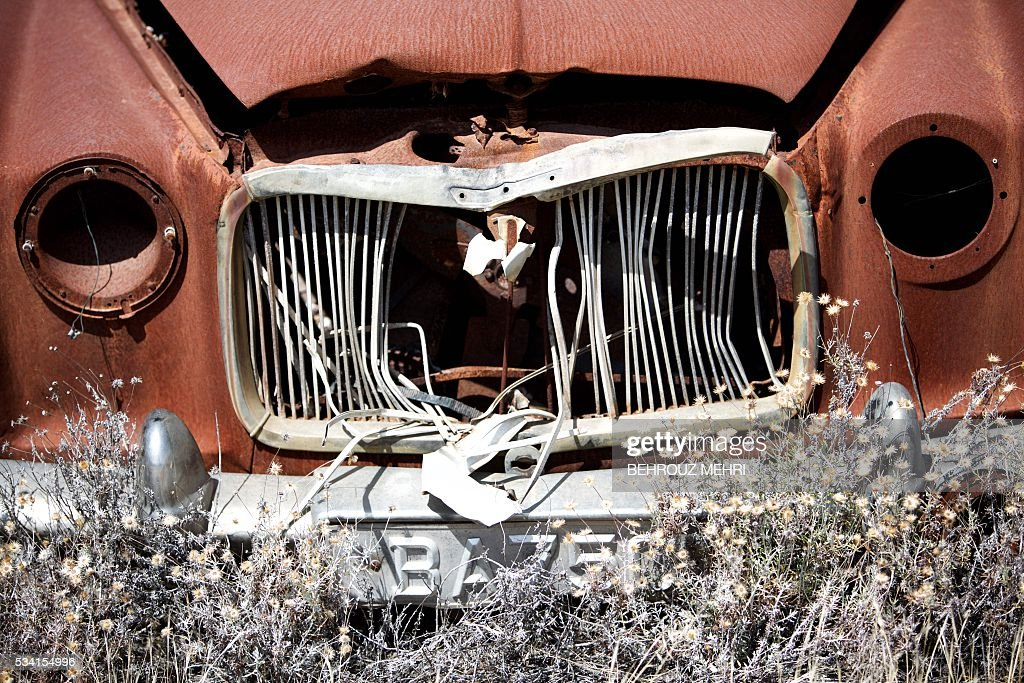 A picture taken on May 25, 2016 shows a close up of an abandoned British Rover car parked at the Sovereign Base Area of Akrotiri, a British overseas territory located ten kilometres west of the Cypriot port city of Limassol. Abandoned in the streets of the base after the war, hundreds of vehicles that belonged to Turkish Cypriots, mostly dating from the 1960s, had been gathered in a vast wasteland in 1975 await their owners on the British base of Akrotiri, 42 years after being left behind in the divided island. The British authorities have recently undertaken an inventory of 400 vehicles in the hope of regaining their former owners, listing images and details of them on an internet site. / AFP / BEHROUZ