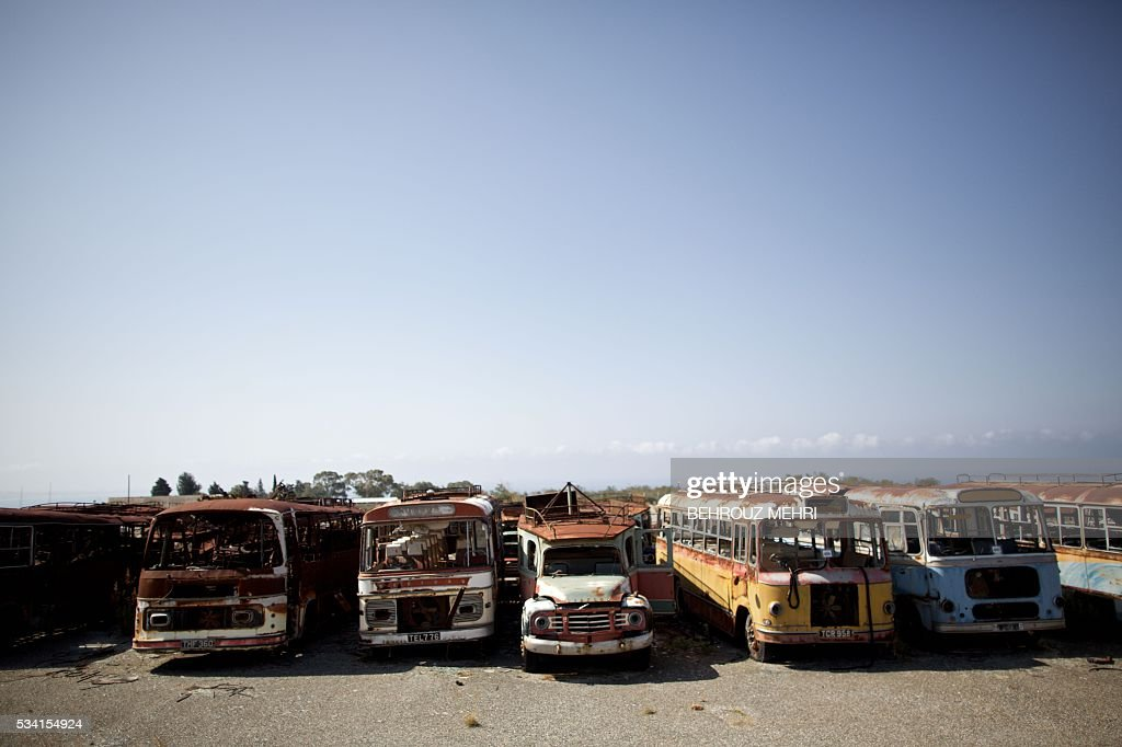 A picture taken on May 25, 2016 shows abandoned Bedford buses parked at the Sovereign Base Area of Akrotiri, a British overseas territory located ten kilometres west of the Cypriot port city of Limassol. Abandoned in the streets of the base after the war, hundreds of vehicles that belonged to Turkish Cypriots, mostly dating from the 1960s, had been gathered in a vast wasteland in 1975 await their owners on the British base of Akrotiri, 42 years after being left behind in the divided island. The British authorities have recently undertaken an inventory of 400 vehicles in the hope of regaining their former owners, listing images and details of them on an internet site. / AFP / BEHROUZ