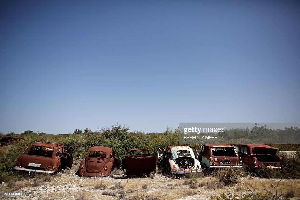 A picture taken on May 25, 2016 shows abandoned cars parked at the Sovereign Base Area of Akrotiri, a British overseas territory located ten kilometres west of the Cypriot port city of Limassol. Abandoned in the streets of the base after the war, hundreds of vehicles that belonged to Turkish Cypriots, mostly dating from the 1960s, had been gathered in a vast wasteland in 1975 await their owners on the British base of Akrotiri, 42 years after being left behind in the divided island. The British authorities have recently undertaken an inventory of 400 vehicles in the hope of regaining their former owners, listing images and details of them on an internet site. / AFP / BEHROUZ