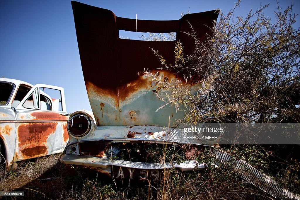 A picture taken on May 25, 2016 shows an abandoned 1960s Ford Anglia parked at the Sovereign Base Area of Akrotiri, a British overseas territory located ten kilometres west of the Cypriot port city of Limassol. Abandoned in the streets of the base after the war, hundreds of vehicles that belonged to Turkish Cypriots, mostly dating from the 1960s, had been gathered in a vast wasteland in 1975 await their owners on the British base of Akrotiri, 42 years after being left behind in the divided island. The British authorities have recently undertaken an inventory of 400 vehicles in the hope of regaining their former owners, listing images and details of them on an internet site. / AFP / BEHROUZ