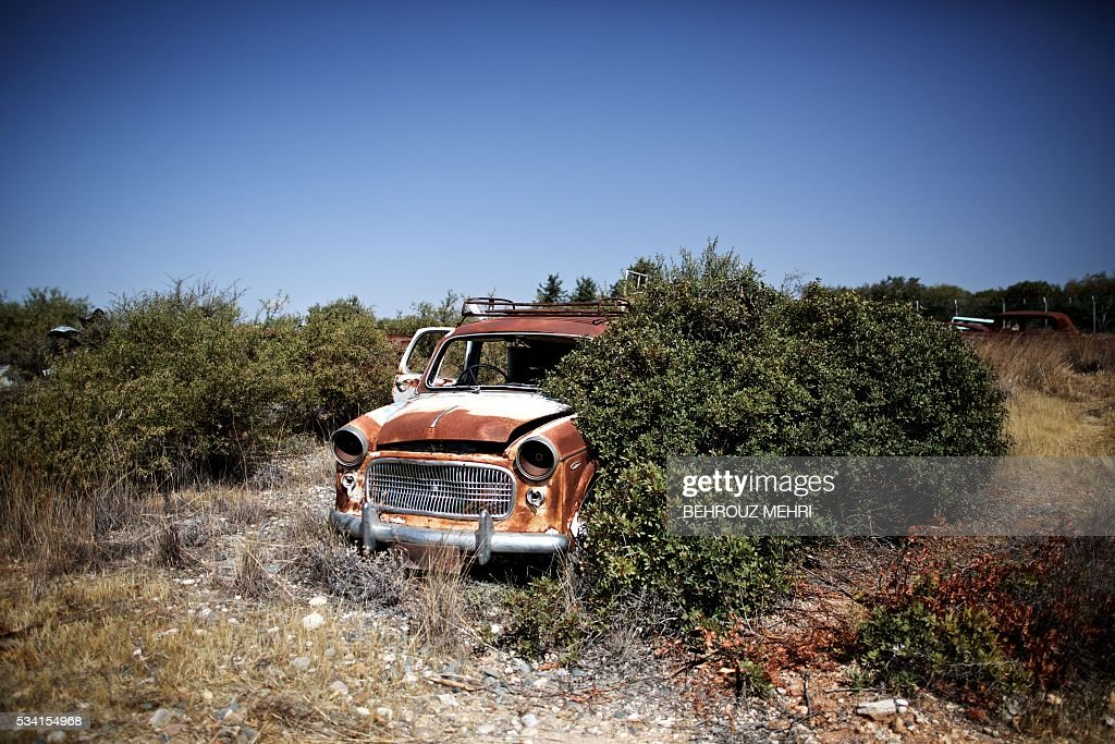 A picture taken on May 25, 2016 shows an abandoned Mini car parked at the Sovereign Base Area of Akrotiri, a British overseas territory located ten kilometres west of the Cypriot port city of Limassol. Abandoned in the streets of the base after the war, hundreds of vehicles that belonged to Turkish Cypriots, mostly dating from the 1960s, had been gathered in a vast wasteland in 1975 await their owners on the British base of Akrotiri, 42 years after being left behind in the divided island. The British authorities have recently undertaken an inventory of 400 vehicles in the hope of regaining their former owners, listing images and details of them on an internet site. / AFP / BEHROUZ