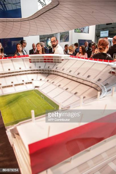 A picture taken on May 25 2016 shows people gathering around the maquette of the Eurostadium Stadium in Brussels during the presentation of the...
