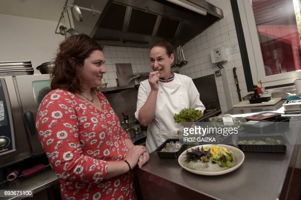 A picture taken on May 25 2017 in Biarritz shows French chef Andree Rosier tasting flowers coming from the aquaponic farm of Lucille Bonnet at her...