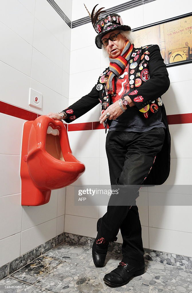 Picture taken on May 26, 2011 shows owner of a Rolling Stones fans museum, Ulrich Schroeder posing next to an urinal in the shape of the group's famous 'tongue' logo in the museum in Luechow, eastern Germany. The museum that opens its doors on April 27, 2012 shows 'thousands of pieces' of memorabilia, including the original signed pool table the group took on tour, instruments, posters and a Stones pinball machine. AFP PHOTO / PHILIPP SCHULZE GERMANY OUT