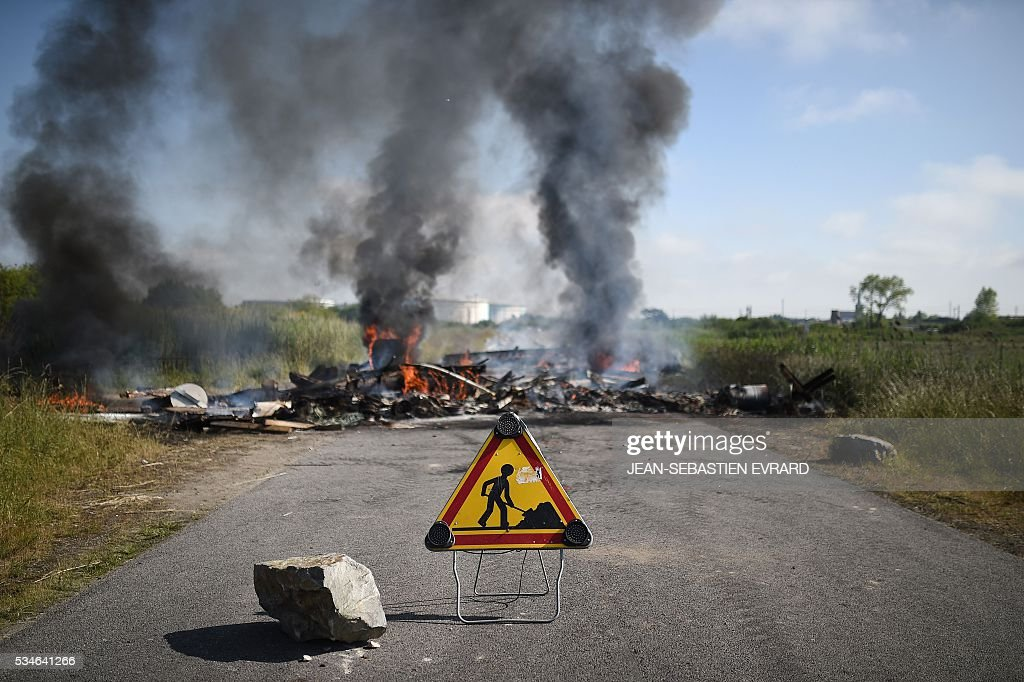 A picture taken on May 27, 2016 shows tires on fire in front of an oil depot near the Total refinery of Donges, western france, after the evacuation of strikers by riot policemen as they block the access to protest against the government's planned labour law reforms. The French government's labour market proposals, which are designed to make it easier for companies to hire and fire, have sparked a series of nationwide protests and strikes over the past three months. French unions on May 27 called on workers to 'continue and step up their action', as a wave of strikes against a disputed labour law disrupted transport and fuel supplies. / AFP / JEAN