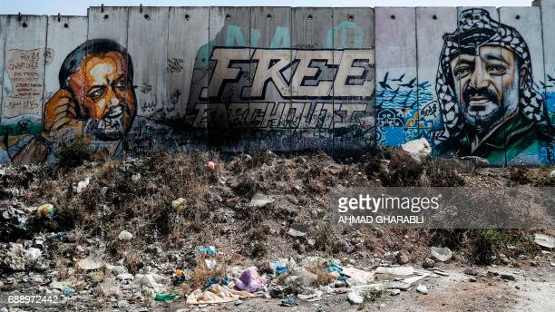 A picture taken on May 27 2017 between Jerusalem and the West Bank city of Ramallah shows a mural of Fatah leader Marwan Barghuti and late...