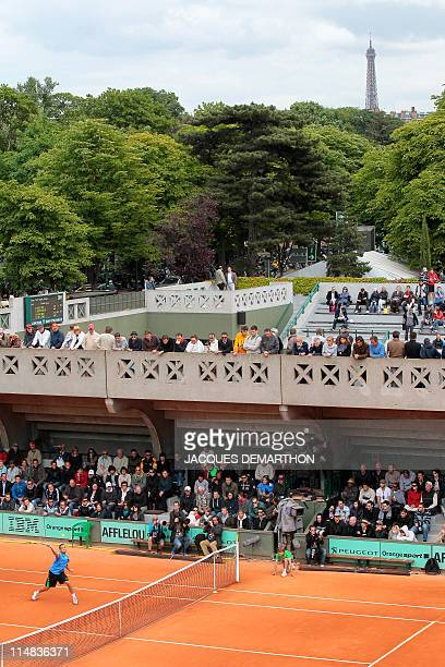 A picture taken on May 27 in Paris shows people looking at a match at the Roland Garros stadium during the French Open tennis championship At...