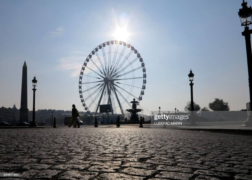 Picture taken, on May 27, 2016, shows a woman passing by the Concorde square in Paris. / AFP / LUDOVIC