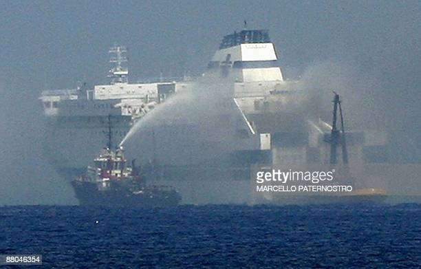 A picture taken on May 29 2009 shows a boat trying to extinguish a fire on a Tirrenia di Navigazione ferry after fire broke out on board prompting...