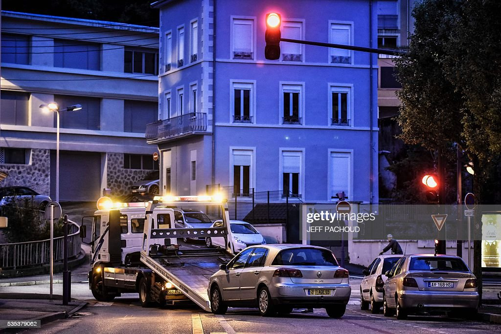 A picture taken on May 29, 2016 in Tarare, near Lyon, central eastern France shows a towing operation by the gendarmes of a car belonging to a suspect after the murder of a mother of three. The woman was found dead on May 29 in Pontcharra-sur-Turdine, near Lyon. Her ex-husband, suspected of the murder, took their three children to his sister's house then surrendered to police. Earlier in the day the 'Plan Alerte Enlevement', for an abduction alert procedure, was triggered following the disparition of the children. / AFP / JEFF