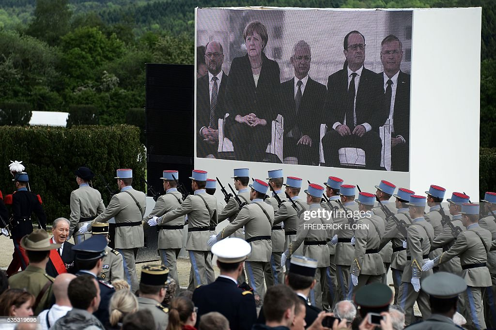 A picture taken on May 29, 2016 shows a screen with German Chancellor and French President attending a remembrance ceremony to mark the centenary of the battle of Verdun, at the Douaumont Ossuary (Ossuaire de Douaumont), northeastern France. The battle of Verdun, in 1916, was one of the bloodiest episodes of World War I. The offensive which lasted 300 days claimed more than 300,000 lives. / AFP / FREDERICK
