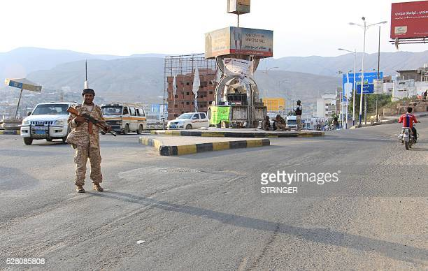 A picture taken on May 3 2016 shows a Yemeni security forces member patrolling a street with a banner hung by AlQaeda militants announcing Islamists'...