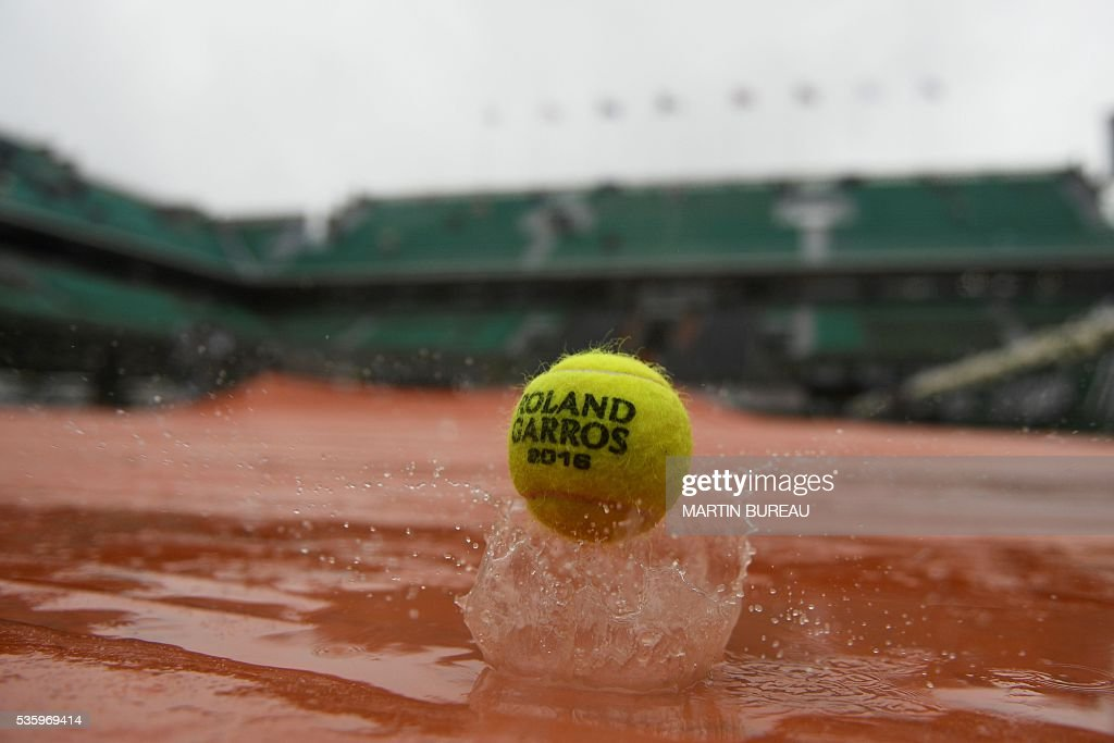 A picture taken on May 31, 2016 an official ball on the tarp covering the Philippe Chatrier central court as the rains falls over the Roland Garros stadium during the Roland Garros 2016 French Tennis Open in Paris on May 31, 2016. / AFP / MARTIN