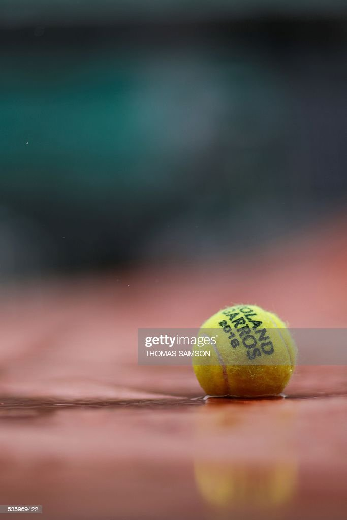 A picture taken on May 31, 2016 an official ball on the tarp covering the Philippe Chatrier central court as the rains falls over the Roland Garros stadium during the Roland Garros 2016 French Tennis Open in Paris. / AFP / Thomas SAMSON