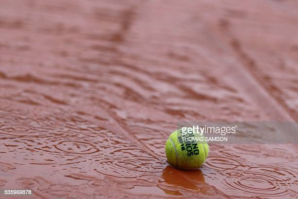 A picture taken on May 31 2016 an official ball on the tarp covering the Philippe Chatrier central court as the rains falls over the Roland Garros...