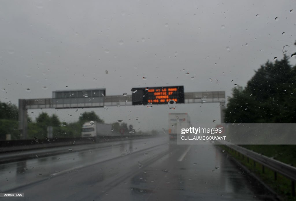 A picture taken on May 31, 2016 between Tours and Orleans, southern Paris, shows lorries driving and an electronical information sign on the A10 highway as heavy rainfalls have disrupted the traffic between Paris and Orleans. The Loiret department is under flood alert and France's weather agency Meteo France maintained today 18 departments under orange alert. SOUVANT