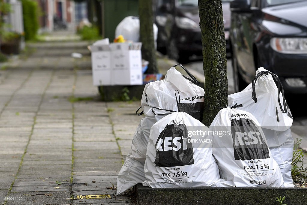 A picture taken on May 31, 2016 shows trash bags in a street of Antwerp during a strike of the public sector staff protesting against centre-right government's austerity plans. Thousands of trade union members took part in peaceful protests in Brussels and other cities during the latest walkout at schools, city transport networks, airports and government offices. / AFP / BELGA / DIRK WAEM / Belgium OUT