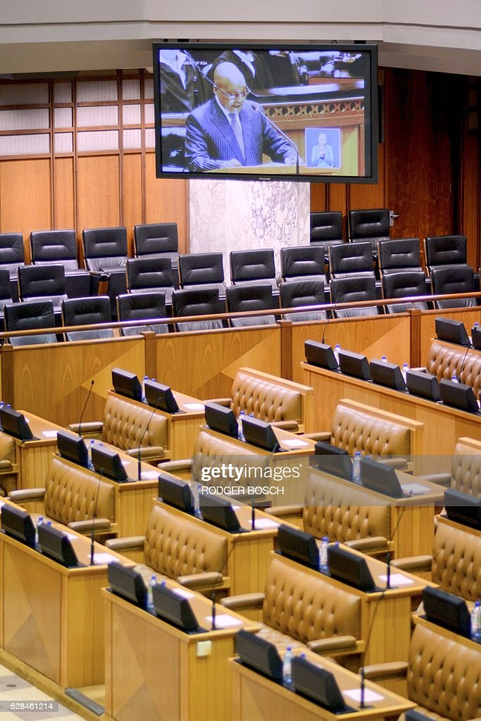 A picture taken on May 5, 2016 shows empty seats and a monitor broadcasting the speech of South African President, Jacob Zuma, at the South African Parliament, as most of the opposition parties were boycotted or suspended from the sitting, in Cape Town. / AFP / RODGER