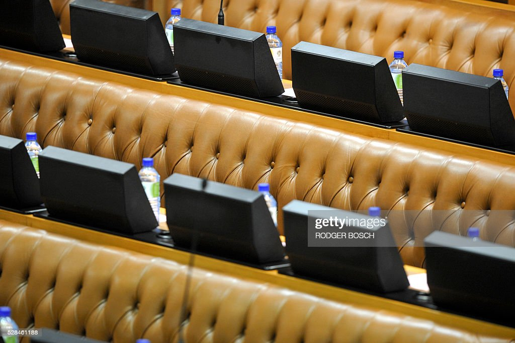 A picture taken on May 5, 2016 shows water bottles placed at empty seats at the South African Parliament, as most of the opposition parties were boycotted or suspended from the sitting, in Cape Town. / AFP / RODGER