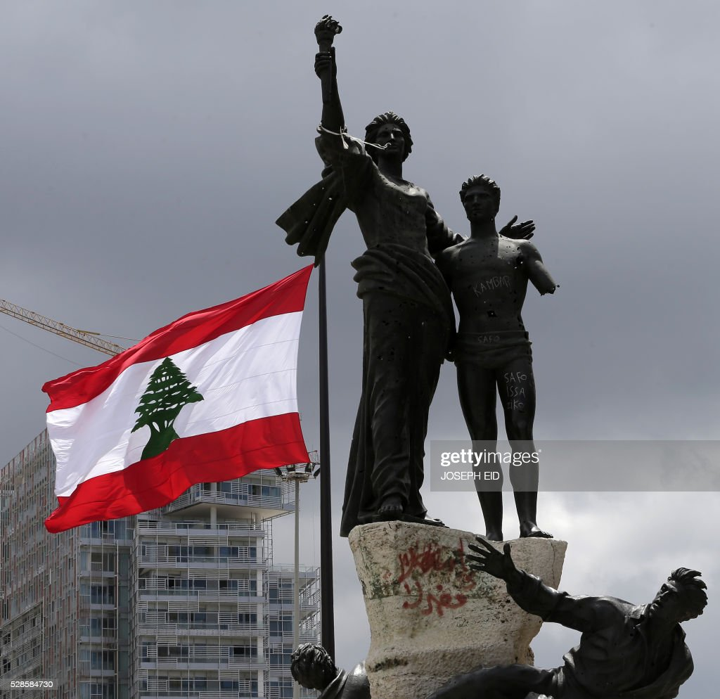 A picture taken on May 6, 2016 shows a giant Lebanese flag fluttering next to the landmark Martyrs Statue in Martyrs square in central Beirut at the occasion of the 100 years since the hanging in public of several Lebanese nationalists who opposed the Ottoman rule during World War I on May 6, 1916. / AFP / JOSEPH EID