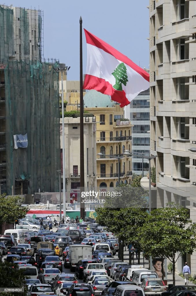 A picture taken on May 6, 2016 shows vehicles driving past a giant Lebanese flag fluttering in central Beirut at the occasion of the 100 years since the hanging in public of several Lebanese nationalists who opposed the Ottoman rule during World War I on May 6, 1916. / AFP / JOSEPH EID