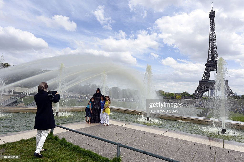 A picture taken on May 9, 2013 in Paris shows a family posing at the Trocadero fountains in front of the Eiffel Tower.