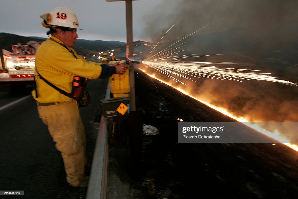 Picture taken on Monday Castaic Area CA – LACFD cap Bill Travis shooting a flair gun from I5 to set up back fire A spot fire from the Day Fire that...
