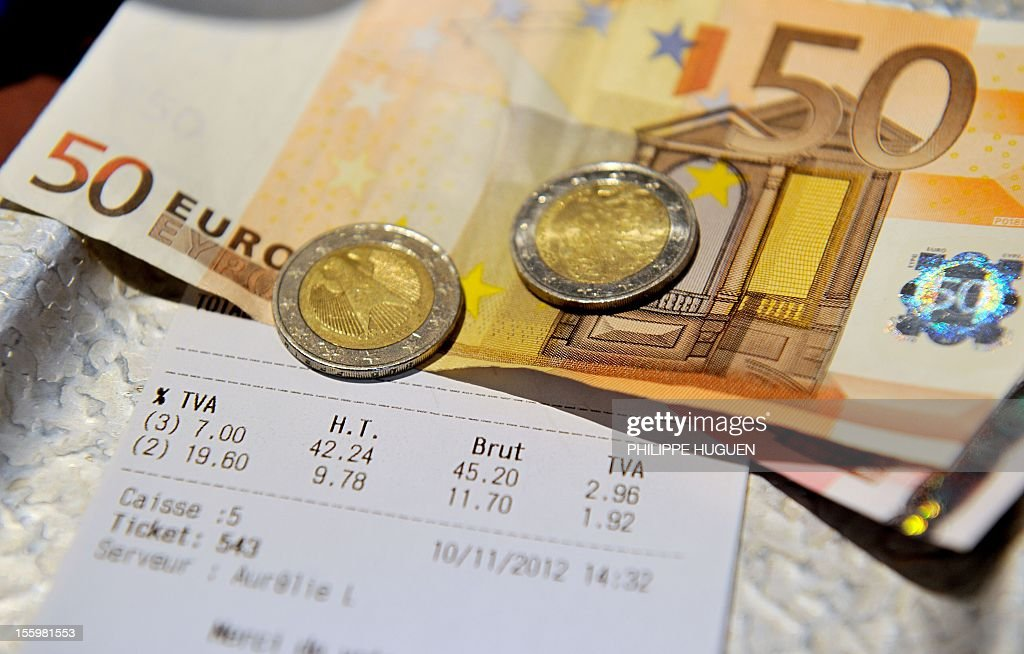 A picture taken on November 10, 2012 in a restaurant in Lille shows euro coins and bank notes set up on a bill with the 19,60 percent value added tax (VAT), and the 7 percent VAT rate. The government announced on November 6, 2012 plans to increase VAT from 19,60% to 20% which is applied to alcoholic drinks sold in bars, cafes and restaurants. The move to increase the rate of value added tax (VAT) charged on restaurant food and hotel accommodation as well, from seven to 10 percent was dubbed 'brutal' by the trade with representative bodies warning it will cost tens of thousands of jobs.