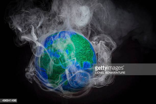 A picture taken on November 10 2015 shows a small globe surrounded by smoke to illustrate global warming France will be hosting and presiding the...